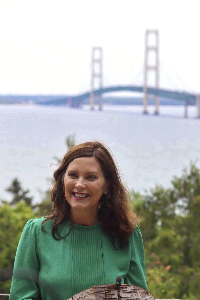 """In this June 10, 2021 photo provided by the Michigan Office of the Governor, Gov. Gretchen Whitmer speaks at Straits State Park in St. Ignace, Mich., with the Mackinac Bridge behind her. Whitmer called for spending a """"historic"""" $250 million in federal coronavirus relief aid to upgrade state parks and trails, a day after Senate Republicans announced a $1.5 billion plan to fix deteriorating local bridges across Michigan. (Michigan Office of the Governor via AP)"""