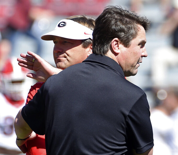 FILE - In this Oct. 9, 2016, file photo, Georgia head coach Kirby Smart, left, and South Carolina head coach Will Muschamp meet on the field before an NCAA college football game in Columbia, S.C. Kirby Smart remembers a time he didn't feel like he could call Georgia teammate Will Muschamp a good friend. After all, Smart was just starting his playing career in 1994 and Muschamp was a senior. Now they will continue their SEC coaching rivalry when Smart's No. 3 Georgia team plays Muschamp's South Carolina team on Saturday. (AP Photo/Rainier Ehrhardt, File)