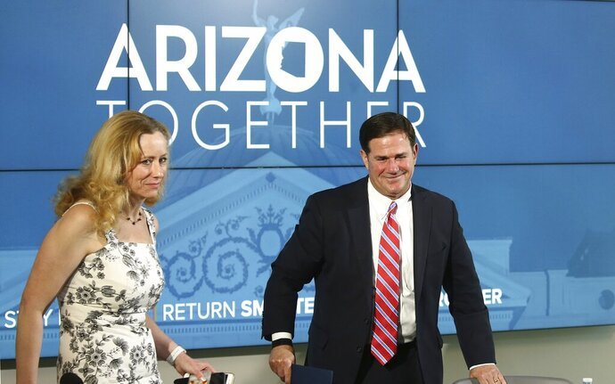 Arizona Gov. Doug Ducey Dr. Cara Christ, Director of Arizona Department of Health Services, left, depart after speaking about the state's most recent coronavirus data during a news conference Thursday, May 28, 2020, in Phoenix. (AP Photo/Ross D. Franklin, Pool)