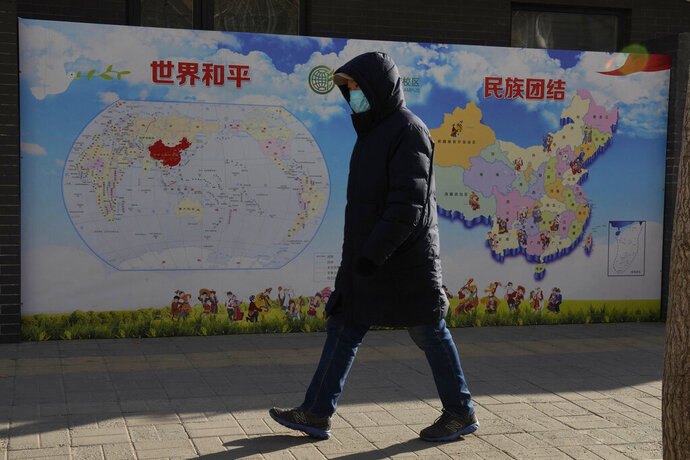 A man walks past a poster with the slogans