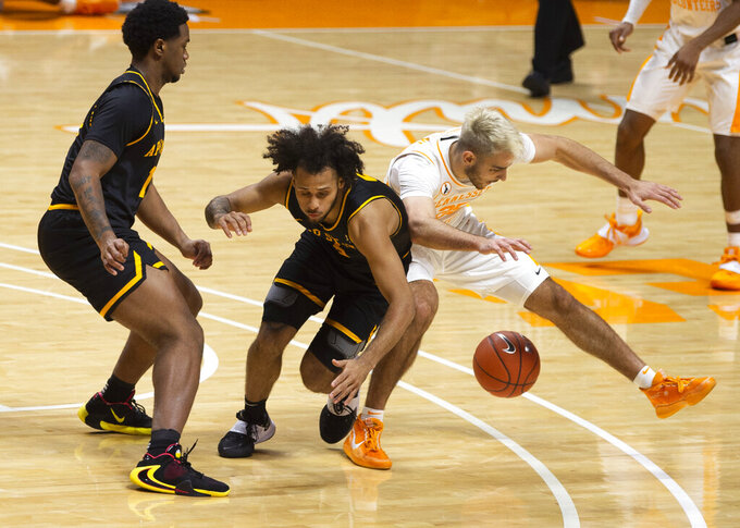 Appalachian State guard Michael Almonacy (5) and Tennessee guard Santiago Vescovi (25) get tangled up during an NCAA college basketball game in Knoxville, Tenn., on Tuesday, Dec. 15, 2020.  (Brianna Paciorka/Knoxville News Sentinel via AP)