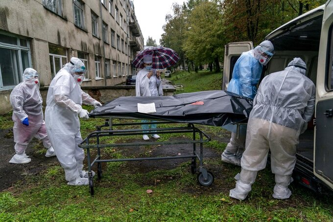 Medical workers move the body of a patient who died from the coronavirus at a hospital in Stebnyk, Ukraine, on Wednesday, Sept. 30, 2020. As coronavirus cases increase, every bed in the hospital in this city in western Ukraine is in use and its chief doctor is watching the surge with alarm and anguish. (AP Photo/Evgeniy Maloletka)