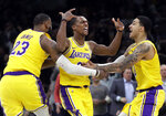 Los Angeles Lakers guard Rajon Rondo, middle, celebrates his game-winning shot with teammates LeBron James (23) and Kyle Kuzma (0), in an NBA basketball game against the Boston Celtics, Thursday, Feb. 7, 2019, in Boston. The Lakers won 129-128. (AP Photo/Elise Amendola)