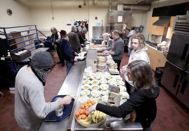 Members of the Madison's homeless population make their way through a dinner line at a men's homeless shelter at Grace Episcopal Church in Madison, Wis. Wednesday, Feb. 19, 2020. Because of limited space, the men have to eat in shifts. (John Hart/Wisconsin State Journal via AP)
