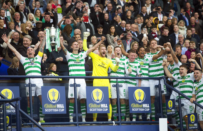 Celtic's Scott Brown, left, and Mikael Lustig celebrate with the trophy after winning the Scottish Cup Final at Hampden Park, Glasgow, Scotland, Saturday, May 25, 2019. Celtic wrapped up a domestic treble for an unprecedented third straight season after beating Hearts 2-1 in the Scottish Cup Final on Saturday. Having already won the Scottish League Cup and league titles, Celtic rallied at Hampden Park with a brace from striker Odsonne Edouard. (Jeff Holmes/PA via AP)