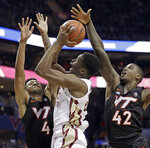 Florida State's Mfiondu Kabengele, center, shoots between Virginia Tech's Nickeil Alexander-Walker (4) and Ty Outlaw (42) during the first half of an NCAA college basketball game in the Atlantic Coast Conference tournament in Charlotte, N.C., Thursday, March 14, 2019. (AP Photo/Nell Redmond)
