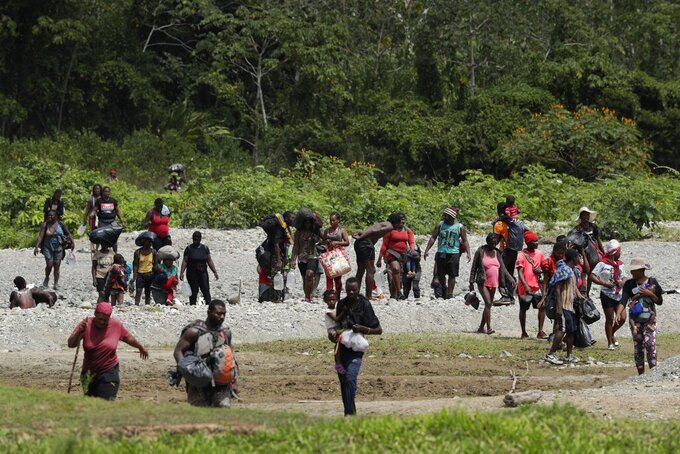 FILE - In this Feb. 10, 2021 file photo, migrants cross the Tuquesa river after a trip on foot through the jungle to Bajo Chiquito, Darien Province, Panama. According to a UNICEF report published Monday, March 29, 2021, the number of migrant children and teenagers moving north through Panama's Darien region has risen drastically since 2017. (AP Photo/Arnulfo Franco, File)