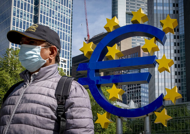 A man walks by the Euro sculpture in front of the old the European Central Bank in Frankfurt, Germany, Tuesday, May 5, 2020. Germany's Constitutional Court has ruled that the country's central bank must stop participating in a key European Central Bank stimulus program but gave the ECB time to demonstrate that the stimulus program is needed and appropriate. (AP Photo/Michael Probst)