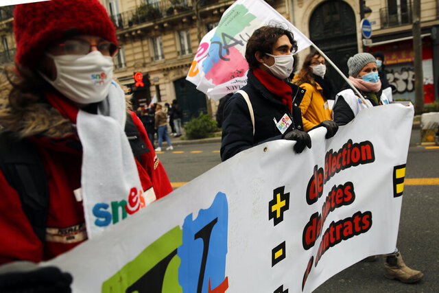 Protestors march during a demonstration in Paris, Tuesday Jan.26, 2021. Schoolteachers and university students marched together in protests or went on strike Tuesday around France to demand more government support amid the pandemic. (AP Photo/Christophe Ena)