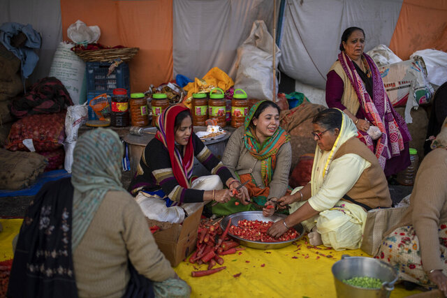 Family members of farmers prepare food for fellow farmers as they block a highway in protest against new farm laws at the Delhi-Uttar Pradesh state border, on the outskirts of New Delhi, India, Monday, Jan. 11, 2021. (AP Photo/Altaf Qadri)