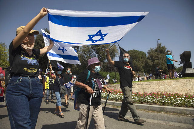 Israeli protesters wave flags and chant slogans during a demonstration against a proposed measure to curtail public demonstrations during the current nationwide lockdown due to the coronavirus pandemic, in front of the Knesset, Israel's parliament in Jerusalem, Tuesday, Sept. 29, 2020.  (AP Photo/Sebastian Scheiner)