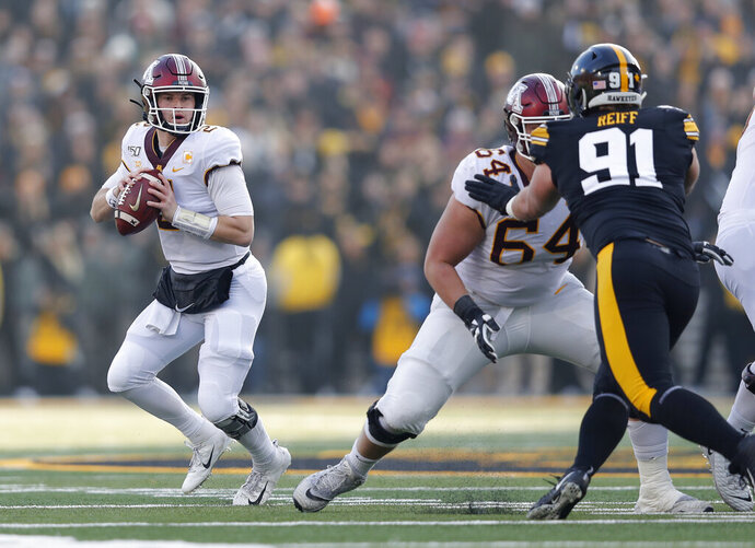 Minnesota quarterback Tanner Morgan, left, drops back to pass during the first half of an NCAA college football game against Iowa, Saturday, Nov. 16, 2019, in Iowa City, Iowa. (AP Photo/Matthew Putney)