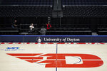 Workers remove chairs from media row inside the arena, Friday, March 13, 2020, in Dayton, Ohio. The coronavirus outbreak has abruptly roused the University of Dayton from its dream of a basketball season. The 29-2 Flyers were rolling into tournament play on a 20-game winning streak that had lifted spirits in an Ohio city battered in the past year by violent deaths and devastation. The NCAA decision to cancel March Madness ended hopes for the small Roman Catholic school's first Final Four appearance in 53 years. (AP Photo/Aaron Doster)