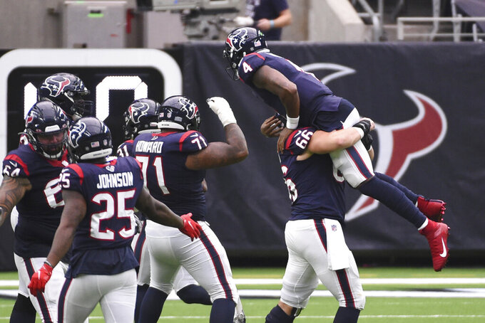 Houston Texans quarterback Deshaun Watson (4) is lifted in the air by teammate Nick Martin (66) as the team celebrates a touchdown against the Jacksonville Jaguars the second half of an NFL football game Sunday, Oct. 11, 2020, in Houston. (AP Photo/Eric Christian Smith)