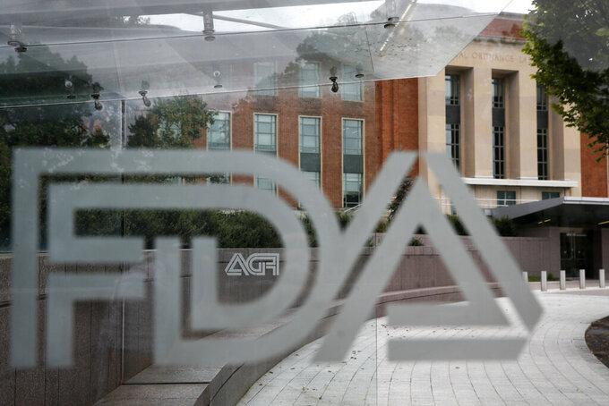 FILE - This Thursday, Aug. 2, 2018, file photo shows the U.S. Food and Drug Administration building behind FDA logos at a bus stop on the agency's campus in Silver Spring, Md. On Friday, Sept. 24, 2021, The Associated Press reported on stories circulating online incorrectly asserting that experts with the Food and Drug Administration revealed that the COVID-19 vaccines are killing at least two people for every person they save. But FDA experts did not say this, and strongly refuted this false claim in an email to The Associated Press. A speaker who is not affiliated with the FDA made these statements during the open public hearing portion of a Sept. 17 FDA vaccine advisory panel meeting. (AP Photo/Jacquelyn Martin, File)