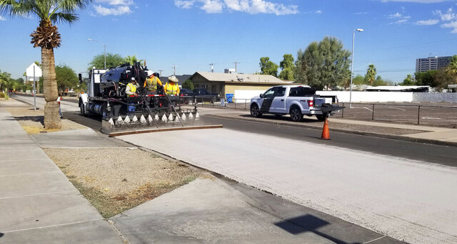 A City of Phoenix Street Transportation Department crew sprays light-colored pavement over blacktop on a street in the Garfield District of Phoenix on Aug. 11, 2020. A team from Arizona State University is working with the city of Phoenix on a pilot program studying the use of