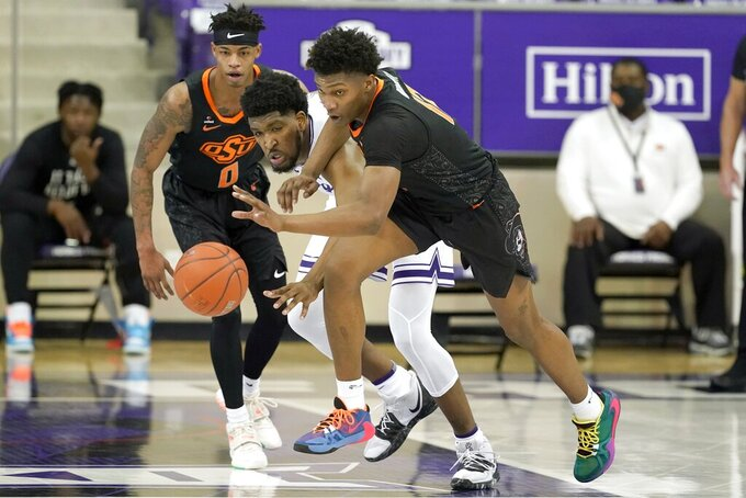 Oklahoma State forward Matthew-Alexander Moncrieffe, right, gets control of a loose ball in front of TCU center Kevin Samuel, center, as Oklahoma State's Avery Anderson III (0) watches the first half of an NCAA college basketball game in Fort Worth, Texas, Wednesday, Feb. 3, 2021. (AP Photo/Tony Gutierrez)