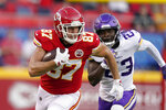 Kansas City Chiefs tight end Travis Kelce (87) runs with the ball as Minnesota Vikings safety Xavier Woods (23) defends during the first half of an NFL football game Friday, Aug. 27, 2021, in Kansas City, Mo. (AP Photo/Charlie Riedel)