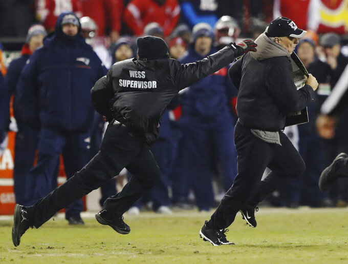 A fan runs to the field as a security chases during the second half of the AFC Championship NFL football game between the Kansas City Chiefs and the New England Patriots, Sunday, Jan. 20, 2019, in Kansas City, Mo. (AP Photo/Charlie Neibergall)