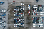In this aerial photo, mid-sized pickup trucks and full-size vans are seen in a parking lot outside a General Motors assembly plant where they are produced Wednesday, March 24, 2021, in Wentzville, Mo.  As the U.S. economy awakens from its pandemic-induced slumber, a vital cog is in short supply: the computer chips that power our cars and other vehicles, and a vast number of other items we take for granted.  Ford, GM and Stellantis have started building vehicles without some computers, putting them in storage with plans to retrofit them later.(AP Photo/Jeff Roberson)