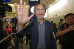 Chinese dissident writer Ma Jian waves to media after arriving Hong Kong international airport, Friday, Nov. 9, 2018. Despite Mallet's rejection, Hong Kong on Friday permitted dissident writer Ma Jian to enter to attend a literary festival, even after an arts venue in the city canceled his appearance. Ma, whose novels frequently satirize China's communist leaders, told reporters he experienced nothing unusual while passing through passport control and that organizers were still lining-up a place for him to speak.