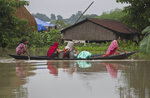 Indian flood affected women transport drinking water on a boat in Burha Burhi village, east of Gauhati, Assam, India, Monday, July 15, 2019. After causing flooding and landslides in Nepal, three rivers are overflowing in northeastern India and submerging parts of the region, affecting the lives of more than 2 million, officials said Monday. (AP Photo/Anupam Nath)