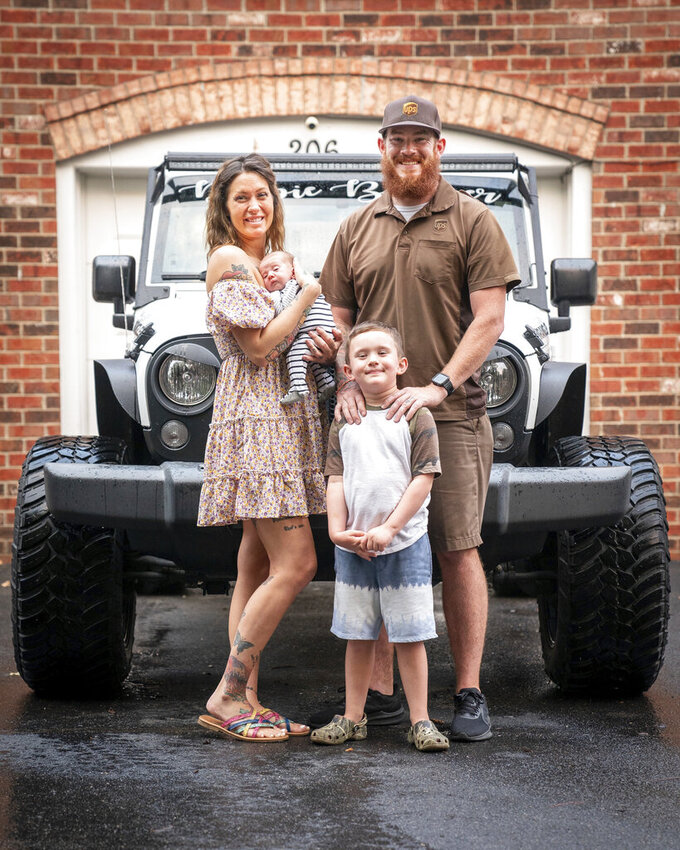 Ryan and Gayla Thompson with their newborn son, Carson, and 5-year-old son, Connor, outside their home in Hermitage, Tenn., Wednesday, July 7, 2021. Gayla gave birth to Carson in their Jeep while her husband Ryan was trying to drive to the hospital. (Andrew Nelles/The Tennessean via AP)