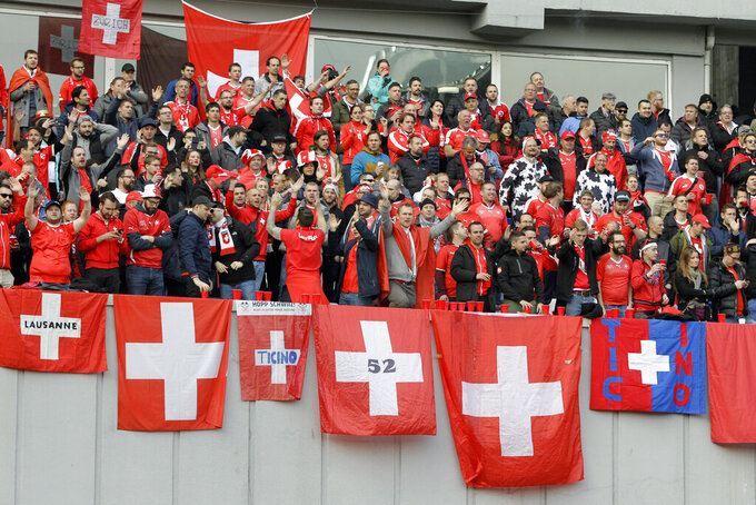 FILE - In this Saturday, March 23, 2019 filer, Switzerland fans shout during the Euro 2020 group D qualifying soccer match between Georgia and Switzerland at Boris Paichadze Erovnuli stadium in Tbilisi, Georgia. With games scattered across 11 cities from London to Baku, this year's European Championship is going to be hard on the fans. Amid the coronavirus pandemic, it remains to be seen how many supporters will be able to attend matches or if any can follow their teams across borders into different countries. (AP Photo/Shakh Aivazov, File)