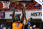 Oklahoma State forward Kalib Boone (22) grabs a rebound next to Oral Roberts guard Carlos Jurgens (11) during the first half of an NCAA college basketball game Tuesday, Dec. 8, 2020, in Stillwater, Okla. (AP Photo/Sue Ogrocki)