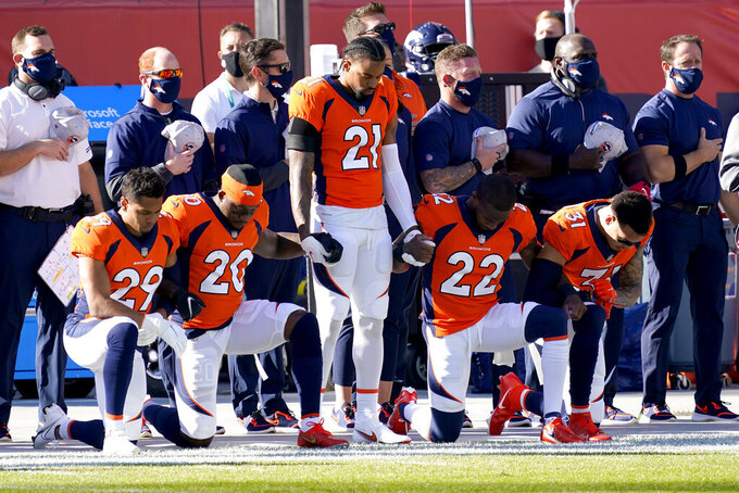 Denver Broncos cornerback A.J. Bouye (21) stands as teammates kneel during the national anthem prior to an NFL football game against the Los Angeles Chargers, Sunday, Nov. 1, 2020, in Denver. (AP Photo/David Zalubowski)