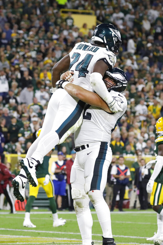 Philadelphia Eagles running back Jordan Howard (24) and center Jason Kelce (62) celebrate a touchdown during the first half of the team's NFL football game against the Green Bay Packers on Thursday, Sept. 26, 2019, in Green Bay, Wis. (AP Photo/Jeffrey Phelps)