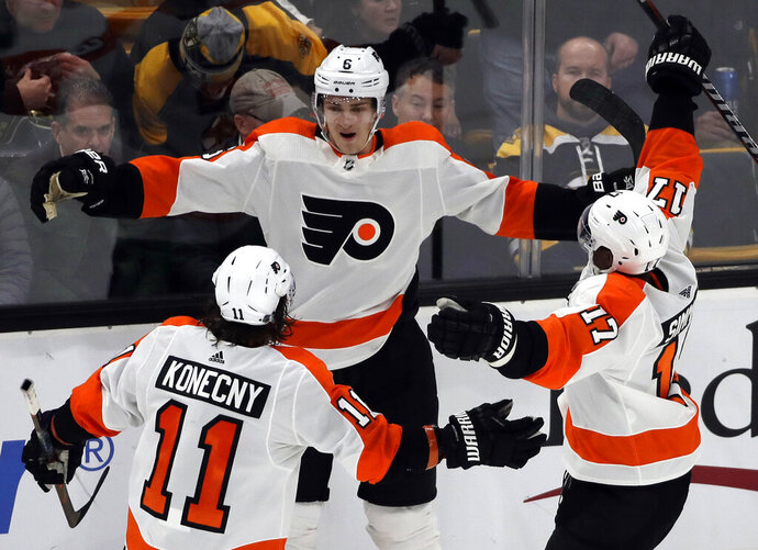 Philadelphia Flyers defenseman Travis Sanheim (6) celebrates his winning goal with teammates Travis Konecny (11) and Wayne Simmonds (17) in the overtime period of an NHL hockey game against the Boston Bruins, Thursday, Jan. 31, 2019, in Boston. (AP Photo/Elise Amendola)