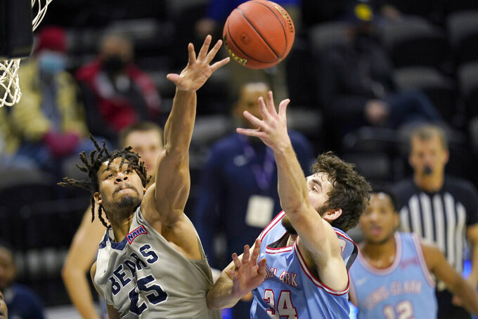 Lewis-Clark State forward Jake Albright (34) shoots while covered by Shawnee State forward Latavious Mitchell (25) during the first half of the NAIA men's college basketball tournament final in Kansas City, Mo., Tuesday, March 23, 2021. (AP Photo/Orlin Wagner)