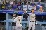 Oakland Athletics' Tommy La Stella (3) is high-fived by Jake Lamb after La Stella scored on a double by Robbie Grossman during the first inning of the team's baseball game against the Los Angeles Dodgers on Wednesday, Sept. 23, 2020, in Los Angeles. (AP Photo/Marcio Jose Sanchez)