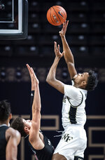 Wake Forest forward Isaiah Mucius (1) shoots over Louisville guard Samuell Williamson during an NCAA college basketball game Wednesday, Jan. 13, 2021, in Winston-Salem, N.C. (Andrew Dye/The Winston-Salem Journal via AP, Pool)
