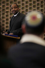 In this Jan. 17, 2020, photo Rev. Dr. Maurice Charles, dean of Rockefeller Memorial Chapel, speaks during the Friday Shabbat Service at KAM Isaiah Israel in Chicago. On the eve of the day set aside to honor an African American who strove against hate and preached racial and social justice, some worry the nation is becoming more divided. (AP Photo/Nam Y. Huh)