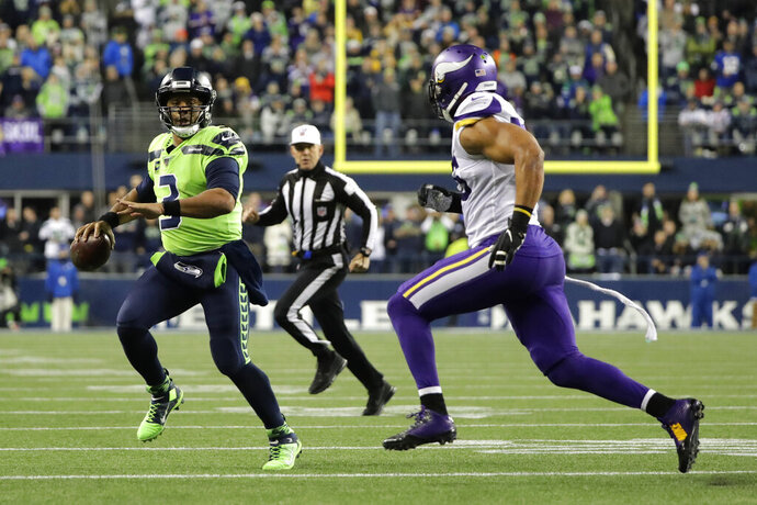 Seattle Seahawks quarterback Russell Wilson (3) scrambles as Minnesota Vikings' Anthony Barr approaches during the first half of an NFL football game, Monday, Dec. 2, 2019, in Seattle. (AP Photo/Ted S. Warren)