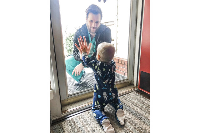 In this photo posted on Facebook, Wednesday, March 25, 2020, by Alyssa Burks, her husband, Dr. Jared Burks, sees his 1-year-old son crawl for the first time, as he touches a glass door from the outside while their son Zeke touches it from the inside of their Jonesboro, Ark. Home. Jared Burks is keeping away from his wife and son because of potential exposure to the coronavirus. Three days after the photo was posted, the family's house was destroyed by a tornado. (Burks Family via AP)