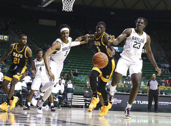 Baylor guard Jordan Turner, left, and teammate forward Jonathan Tchamwa Tchatchoua, right, battle Arkansas-Pine Bluff forward Markedric Bell for the ball in the second half of an NCAA college basketball game, Monday, Dec. 21 2020, in Waco Texas. (Rod Aydelotte/Waco Tribune Herald, via AP)