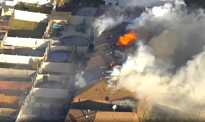 This image made from video provided by WABC-TV shows a fire at connected houses in the Staten Island borough of New York on Monday, Jan. 20, 2020. Six homes are severely damaged and more than 30 people are displaced after the five-alarm fire tore through row houses. (WABC-TV via AP)