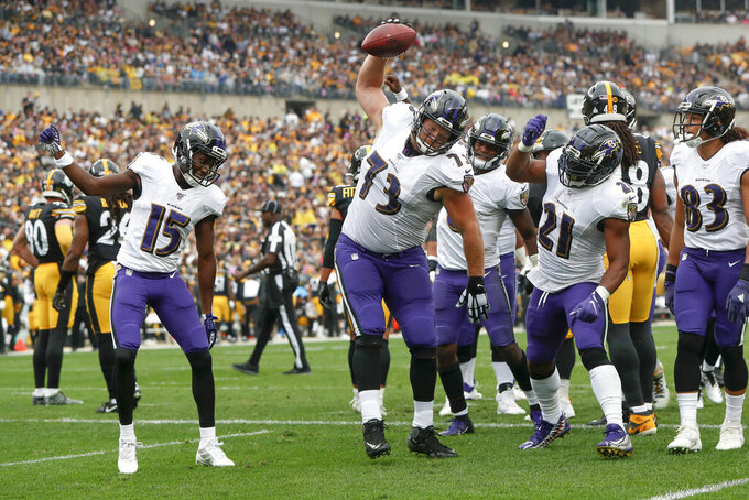Baltimore Ravens offensive guard Marshal Yanda (73) spikes the football as he celebrates with teammates after running back Mark Ingram (21) scored against the Pittsburgh Steelers in the ]first half of an NFL football game, Sunday, Oct. 6, 2019, in Pittsburgh. (AP Photo/Don Wright)