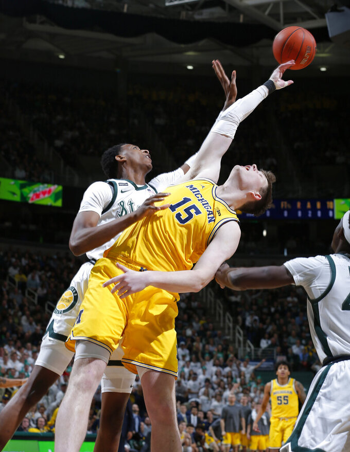 Michigan's Jon Teske (15) and Michigan State's Marcus Bingham Jr. reach for a rebound during the first half of an NCAA college basketball game, Sunday, Jan. 5, 2020, in East Lansing, Mich. (AP Photo/Al Goldis)