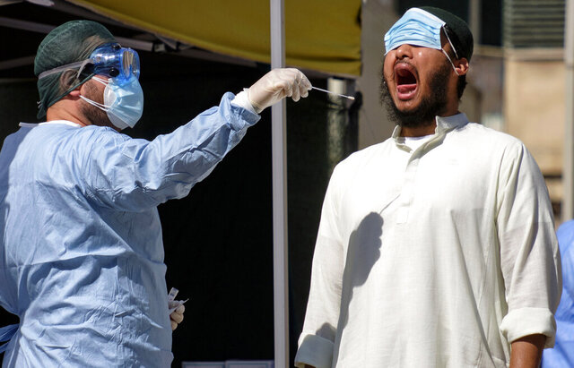 A member of the Bangladeshi immigrant community, right, has a swab being taken to test for COVID-19 outside a healthcare center in Rome, Thursday, July 9, 2020. Italy, the onetime European epicenter of the outbreak, went on alert about possible infections in the Bangladeshi immigrant community after a cluster of about a dozen cases was traced to a recently returning Bangladeshi worker in Rome. (Mauro Scrobogna/LaPresse via AP)