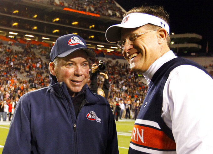 FILE - In this Nov. 22, 2014, file photo, Samford head coach Pat Sullivan, left, meets with Auburn head coach Gus Malzahn before an NCAA college football game in Auburn, Ala. Sullivan, the 1971 Heisman Trophy winner at Auburn who went on to coach TCU and Samford, died Sunday, Dec. 1, 2019. He was 69. (AP Photo/Butch Dill, File)