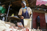 In this photo taken Thursday, June 4, 2020, Margaret Awino, 54, who lost her job after 15 years as a cleaner for a charity, prepares raw chicken to fry in the street to earn some income, in the Kibera slum, or informal settlement, of Nairobi, Kenya. Factories and stores are reopening and economies are reawakening but many jobs just aren't coming back - that's the harsh truth facing workers laid off because of the coronavirus around the U.S. and the world. (AP Photo/Khalil Senosi)