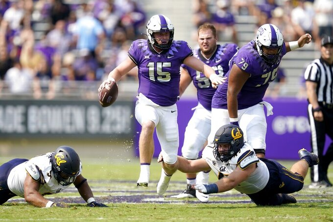 TCU quarterback Max Duggan (15) carries the ball past California defensive end JH Tevis (47) and others for a gain in the first half of an NCAA college football game in Fort Worth, Texas, Saturday, Sept. 11, 2021. (AP Photo/Tony Gutierrez)
