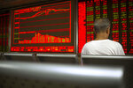 A Chinese investor monitors stock prices at a brokerage house in Beijing, Thursday, June 20, 2019. Asian shares were higher on Thursday, with the Shanghai benchmark up 2.6%, after the Federal Reserve reaffirmed that it's prepared to cut interest rates if needed to shield the U.S. economy from trade conflicts or other threats. (AP Photo/Mark Schiefelbein)