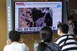 """People watch a TV screen showing a file satellite image of the Yongbyon nuclear site in North Korea during a news program at the Seoul Railway Station in Seoul, South Korea, Monday, Aug. 30, 2021. North Korea appears to have restarted the operation of its main nuclear reactor used to produce weapons fuels, the U.N. atomic agency said, as the North openly threatens to enlarge its nuclear arsenal amid long-dormant nuclear diplomacy with the United States. Korean letters read: """"North Korea's Yongbyon nuclear facility seems to have restarted."""" (AP Photo/Ahn Young-joon)"""