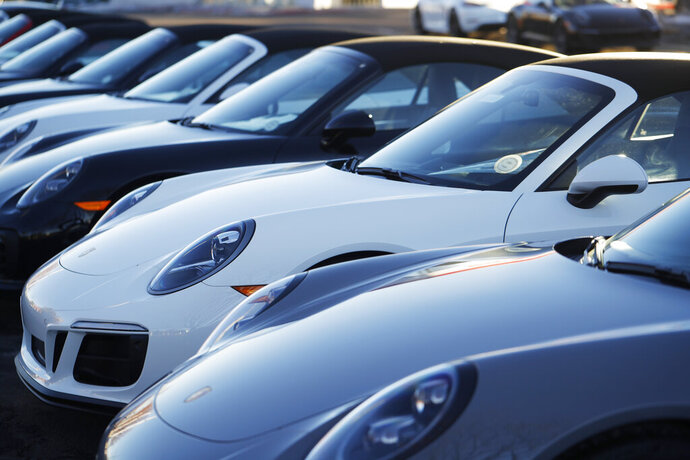 In this Sunday, Feb. 3, 2019, photograph, a long row of unsold 2019 911 Carrera GTS cabriolets sits at a Porsche dealership in Littleton, Colo. Borrowers are behind in their auto loan payments in numbers not seen since delinquencies peaked at the end of 2010, according to the Federal Reserve Bank of New York. (AP Photo/David Zalubowski)