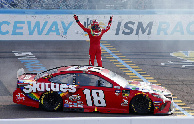 Kyle Busch stands on his race car to acknowledge the fans after winning a NASCAR Cup Series auto race at ISM Raceway, Sunday, March 10, 2019, in Avondale, Ariz. (AP Photo/Ralph Freso)